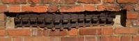 Fragment gąsienicy Borgward B IV (ciężkiego nosiciela ładunków wybuchowych), wmurowany w ścianę Katedry św. Jana w Warszawie (1944 r.).